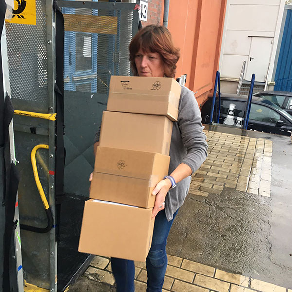 Kaffee Pakete zum Postwagen schleppen